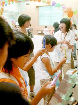 Дети выключают свои сотовые телефоны во время форума по безопасному использованию Интернета, устроенного Министерством внутренних дел и коммуникаций в конце августа