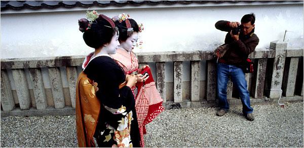 Тайваньский фотограф делает снимок гейш Юкино (слева) и Саюри (справа) в Киото
