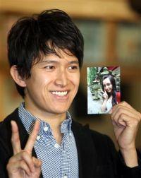 Актёр Цуёси Абэ показывает фотографию своей жены
