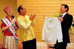 Премьер-министр Таро Асо (справа) получает в подарок рубашку кариюси от губернатора префектуры Окинава (в центре) и Мики Уэти, ставшей Мисс Окинава (слева)