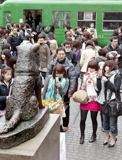 Молоденькие девушки фотографируют популярную статую верной собаки Хатико, которая находится перед станцией Сибуя в Токио. 8-е марта 2009 г.
