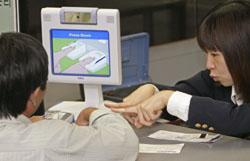 Сотрудница иммиграционной службы демонстрирует представителям СМИ действие системы биометрического контроля. Аэропорт Нарита, ноябрь 2007 г.
