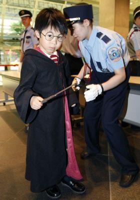 Сотрудница охраны проверяет мальчика в костюме Гарри Поттера перед японской премьерой фильма Гарри Поттер и Принц-полукровка. 6 июля 2009 г., Токио. REUTERS/Kim Kyung-Hoon