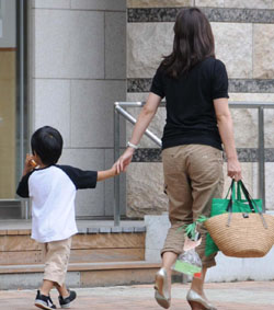 Мать и дитя прогуливаются в парке в токийском районе Минато. 30-е июня 2009 г.