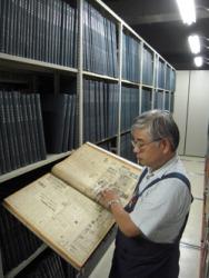 Сотрудник библиотеки держит подшивку старых выпусков Майнити. Центральная библиотека токийского района Адати