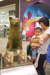Мать с ребёнком рассматривают статую Хатико в кинотеатре Aeon в Микаве, префектура Ямагата