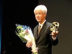 Кититаро Нэгиси с наградой в руках принимает аплодисменты киноманов