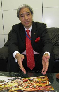Разносчик пиццы: Эрнест Хига, президент Хига Индастриз, владелец предприятия Домино Пицца в Японии, демонстрирует последнее меню в своем офисе в токийском округе Тиёда. Фото Минору Мацутани