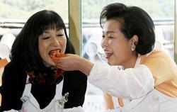 Миюки Хатояма (слева), жена японского премьер-министра Юкио Хатоямы, пробует кимчхи – традиционные корейские соленья – из рук Ким Юн Ок, жены южнокорейского министра Ли Мён Бака. Институт традиционной корейской еды, Сеул, Южная Корея. 9-е октября 2009 г.
