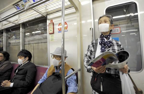 Пассажиры токийского метро носят маски в рамках кампании по предотвращению распространения гриппа H1N1