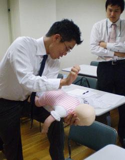 Мужчина осваивает навыки обращения с детьми при помощи куклы-младенца в школе для пап. Тюо, Токио. Ноябрь 2009 г.