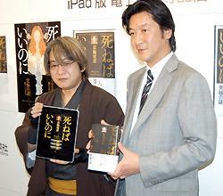 Писатель Нацусико Кёгоку (слева) и вице-председатель издательства Kodansha Ёсинобу Нома в ходе пресс-интервью. Кёгоку держит в руках электронную версию своего романа. 20-е мая 2010 г.