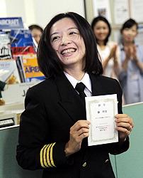 Ари Фудзи, первая женщина-капитан самолёта в основной группе японских авиакомпаний, держит в руках назначение на должность капитана. Икэда, префектура Осака. 9-е июля 2010 г.