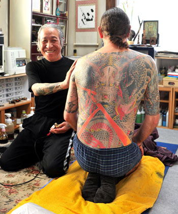 Экспортёр искусства – мастер татуировки Хориёси III позирует для фото после окончания работы на теле одного из австралийских клиентов в своей студии в Иокогаме. 2-е июня 2010 г.