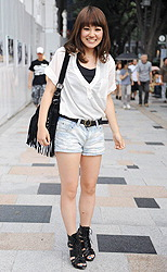 20-летняя студента в джинсовых шортиках и простой белой футболке