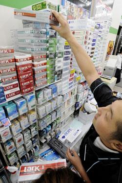 Сотрудник раскладывает блоки сигарет в магазине в токийском районе Минато