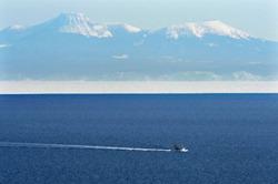Судно пересекает пролив Нэмуро (Кунаширский пролив). На заднем плане видна гора Раусу на о-ве Кунасири (Кунашир). Белая полоса в нижней части острова это айсберг