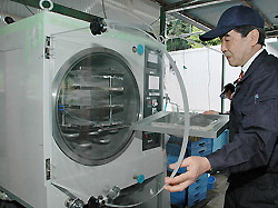 Исао Касинэ (Isao Kashine), президент Kansai Hozon Kagaku Kogyo, помещает мокрые документы в сублимационную сушилку на заводе в городе Нара, 26 мая 2011 года (Mainichi)