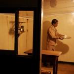 Рабочий несет чаек начальникам, обсуждающим планы на день в соседней комнате