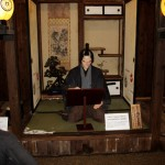 """В центре экспозиции разместили скульптурный портрет Дзюдзаэмона Намбу - основателя промышленной золотодобычи в Осаридзаве. Дело было начато в 1602 году. И под управлением клана Намбу золотые рудники работали вплоть до конца XIX века, когда весь комплекс был перекуплен кланом Ивасаки (теперешний """"Мицубиси""""). На """"занавесках"""" и фонарях - гербы клана Намбу. С XVII века клану принадлежали земли хана Мориока со столицей в одноименном городе. Сейчас город Мориока - столица префектуры Иватэ"""