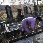 Мужчина приводит в порядок могилу на кладбище в г. Кацурао, 20-е ноября 2011 г.