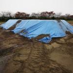 Прикрытая брезентом насыпь из загрязнённой почвы, собранной со спортивной площадки в г. Минамисома. 19-е ноября 2011 г. Заражённая почва заменяется чистой ради защиты детей