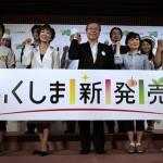 Губернатор префектуры Фукусима Юсэй Сато (в центре), жители префектуры и те, кто их поддерживает, позируют фотографам в ходе мероприятия в Токио, организованного с целью продвижения товаров из префектуры. Надпись на плакате: «Новые товары из Фукусимы». Фото от 17-го августа 2011 г. Многие в стране беспокоятся касательно безопасности фукусимских продуктов, уровень радиации в которых зачастую превышает установленные правительством границы