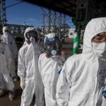 Работники в защитных костюмах и масках входят в центр управления в ЧС на АЭС «Фукусима-1». Окума, 12-е ноября 2011 г.