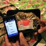 На смартфоне демонстрируются результаты проверки на радиацию грибов маитакэ, проведённой компанией-производителем. Рынок в Токио, 12-е сентября 2011 г. В данном случае грибы не заражены