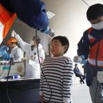 Мальчик проходит радиационный тест прежде чем войти в эвакуационный центр. Фукусима, 1-е апреля 2011 г.