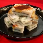 """Суси. Разновидность """"хако-дзуси"""", т.е. """"суси прессованные в коробке"""". Считается, что эта разновидность суси появилась в Кансае. В коробку плотно набивается рис и переслаивается всякими морепродуктами и/или чем придется. Потом этот """"слоеный пирог"""" вытряхивается из коробки и нарезается кусками. Вот это все тут и видно"""