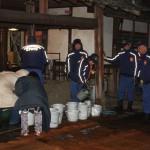 Добровольцы-служители, наполняющие ведра водой из храмового колодца