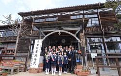 Последние выпускники начальной школы Фукия позируют вместе со своими учителями перед зданием школы. Такахаси, префектура Окаяма. 20-е марта
