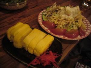 Омлет рулончиком дасимаки с маринованным имбирем и фирменный салат заведения. На самом деле, это ассорти из нескольких салатов на одной тарелке плюс некоторое количество просто свежих порезанных овощей. Семейная такая тарелка, каждый может цапнуть, что больше хочется