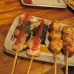 Слева на тарелке - кусочки грудки. Зеленое - аосисо (зеленая перилла), красное сверху - пюре из маринованных слив. Рядом - шарики из куриного фарша с зеленью
