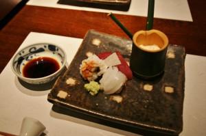"""Сасими. Белое """"кудлатое"""" - рыба """"хамо"""" (правда, не сырая, обваренная) с каплей соуса из соленой сливы. Белое полосками - кальмар сырой. Красное - тунец. Торчит треугольничек белого между рыбами - кусочек сырого нага-имо (вроде """"картошки"""" местной). В обрезке бамбука - юба (пенка соевого молока)"""