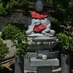 Дзидзо-сан с ребенком, пытающимся спрятаться под его передничек