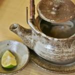 """Это разновидность супа. Называется """"добин-муси"""" 土瓶蒸し. Первая часть слова - 土瓶 - означает """"керамический чайник"""", в котором блюдо готовится и подается. Вторая - 蒸し - """"готовка на пару"""". Это чаще всего сезонное блюдо, осеннее. Готовится из самых дорогих японских осенних грибов мацутакэ с добавлением всякого прочего. Конкретно тут - креветка и зеленая трава мидзуна. В чайнике и на пару готовится для того, чтобы максимально сохранить деликатный вкус и аромат грибов. С цитрусом можно поступить как больше нравится. Можно проигнорировать, если вы не любите кислое. Можно выжать целиком прямо в чайник. Можно капать понемногу в суп, налитый в плошечку. Или через раз, чтобы оценить разницу. Можно бросить этот кусок в чайник, чтоб суп приобрел и немного аромата шкурки судати. Выпив жидкость из плошечки, условно-твердое содержимое чайника поедается прямо из него же палочками"""
