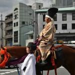 Вот этот серьезный дедушка - один из городского или префектурального начальства. В таких же костюмчиках начальство повыше, включая мэра и губернатора, ехало в открытых каретах. А этого дедушку посадили верхом. Костюмчик на нем - примерно времен Камакуры, когда самурайство таки выделилось в конкретную силу. И костюмно - тоже