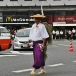 """Сандзёниси Суэтомо - один из семерки дворцовых аристократов, членов радикальной антизападной группировки сторонников Мэйдзи. В сентябре 1863 года, потерпев поражение от более умеренно-настроенных членов императорской партии, бежали из Киото во главе со своим лидером принцем Сандзё Санэтоми. После того, как последний из Токугава отказался от власти в пользу императора, вернулись к активной политической жизни и занимали важные посты в правительстве Мэйдзи. Этот фрагмент шествия как раз показывает бегство из Киото дождливой сентябрьской ночью (потому и """"плащик"""" из рисовой соломы на плечах)"""