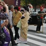 Это гейша, в рабочем наряде. Утверждают, что в основных ролях женских персонажей Дзидай Мацури обычно выступают гейши Киото. Им привычнее носить исторический макияж (который для гейш является рабочим и практически ежедневным) и костюмы (благо современный наряд гейши не очень сильно отличается от исторических). Ну, и привычка постоянно находиться в центре внимания тоже не последняя причина. Гейши, не задействованные в параде, часто ходят смотреть на своих подруг. И полюбоваться, и морально поддержать. Так что увидеть гейшу среди зрителей парада - не такая уж редкость