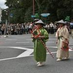Процессия делится на собственно танцоров и музыкантов сопровождения. Вот эти дамы в ярких нарядах - как раз оркестр. Красно-белые палки у них в руках - держатели для гонга, в который стучат маленькой палочкой (как дама на переднем плане)