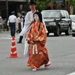 О-Тятя, Леди Ёдо, Ёдо-доно. Красавица конца XVI века. Вторая жена Тоётоми Хидэёси, сполна разделившая с ним и могущество, и гибель всех надежд. Единственная из всех женщин Хидэёси смогла родить ему сыновей, первый из которых умер во младенчестве, а второй стал наследником могущественного кампаку. После смерти Тоётоми Хидэёси власть в Японии перехватил его бывший вассал Токугава Иэясу. Планам Иэясу на полное объединение Японии под одной властью мешал наследник Хидэёси, как полноценный и законный претендент на эту влать. Войска Токугавы атаковали осакский замок, единственный оставшийся у Ёдо-доно и ее сына Хидэёри. Когда стало ясно, что замок не удержать, Ёдо-доно и Хидэёри покончили жизнь самоубийством. На параде девушка идет в косодэ, полностью копирующем реальное платье, принадлежавшее Ёдо-доно