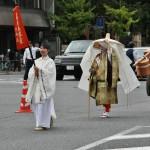 Дама из могущественного семейства Фудзивара. Фудзивара-но Абуцуни, жившая в XIII веке. Жена поэта Фудзивара-но Садаиэ (Тэйкэ) и мать поэта Фудзивара-но Тамэиэ сама была писательницей. В сохранившихся дневниках Абуцуни есть описание костюма путешествующей дамы из аристократической семьи. Именно в этом костюме и представлена на параде писательница. За ней идет слуга с багажом и провиантом на дорогу.