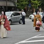 """Красавица, жившая на грани эпох Хэйан и Камакура. Сидзука Годзэн, леди Сидзука - одна из известнейших женщин японской истории, героиня эпоса того времени """"Хэйкэ Моногатари"""". Была сирабёси, танцовщицей из знатной семьи. Именно в этом костюме и представлена на параде. За ней идет ее фрейлина в традиционном благородном женском наряде того времени. Современные гейши считают сирабёси своими предсшественницами. Сирабёси развлекали знатных аристократов танцами, игрой на музыкальных инструментах и изящной беседой. Сами происходившие из знатных семей и получившие прекрасное для того времени образование, сирабёси часто становились женами и наложницами аристократов. Сидзука Годзэн была любовницей Минамото-но Ёсицунэ, брата первого сёгуна Камакуры Минамото-но Ёритомо и его политического противника. Будучи беременной, была захвачена войсками Ёритомо и принуждена танцевать для него. Во время танца пела о своей любви к Ёсицунэ. Разозленный Ёритомо готов был немедленно расправиться с танцовщицей, но жена попыталась уговорить его отпусть Сизуку. Ёритомо поставил условие: если у Сизуки родится дочь, он отпустит обеих. Но если будет сын, его придется убить, чтобы не пытался составить конкуренции в борьбе за власть. У Сидзуки Годзэн родился сын. Пытаясь спасти сына, леди Годзэн отдала ребенка своей матери и сама сбежала. Позже Ёритомо таки захватил леди Годзэн вместе с сыном и убил обоих"""