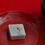 Чай с конфеткой. На конфетке вытеснено изображение Золотого Павильона и прилеплена пара лепесточков натурального золота