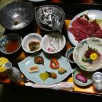 """Один из столиков. Слева большая серебристая плошка с куском морской капусты """"комбу"""" - это для набэ, вариант """"сябу-сябу"""". Мясо и овощи для этого едова приготовлены на большой тарелке справа. Мясо - разновидность японской говядины, производимой в Иватэ: """"маэдзава-гю"""""""