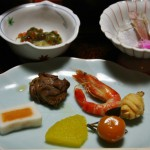 """Закуски. Креветку видно. Белое - тоже разновидность рыбной сосиски-камабоко. Желтое на переднем плане - сваренная в сахарном сиропе шкурка какого-то цитруса. Рыжее круглое - тоже сваренный в сахаре цельный кинкан (кумкват). Круглое справа - корнеплод кувай, в новогодние дни этот овощ (обязательно подается с """"хвостиком""""-побегом) символизирует новые возможности. А коричневая кучка - кажется, содержимое морского ежа, тушеное в соевом соусе с сахаром"""