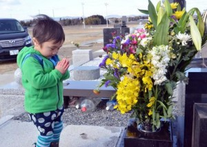Мальчик молится о покое для своих родственников, погибших в результате цунами в 2011 году. Минамисома, префектура Фукусима. 11-е марта 2013 года