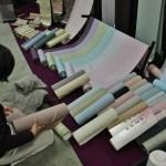 Девушка рассматривает ткани для иромудзи - монотонные кимоно, без рисунка. В зависимости от количества гербов такое кимоно может быть как полуформальным, так и вполне формальным